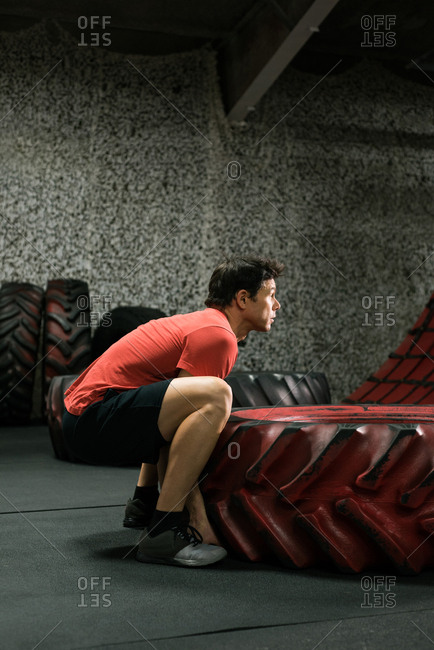 Muscular man flipping tire at the gym