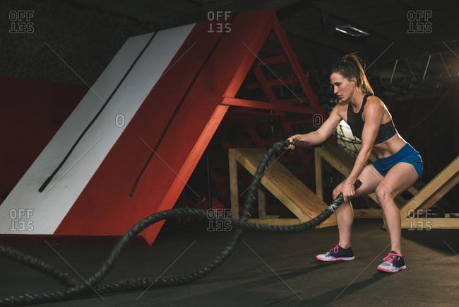 muscular woman exercising with battle rope at gym