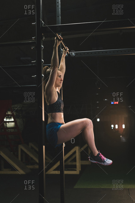 Muscular woman practicing pull up on a pull up bar at the gym