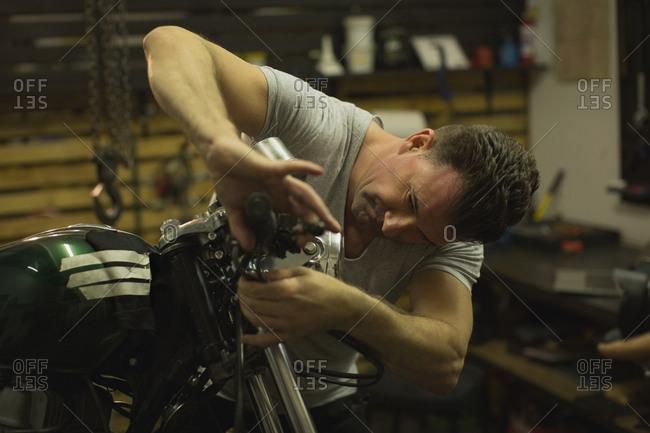 Mechanic checking a motorbike brakes in garage
