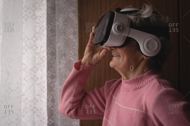 Senior woman using virtual reality headset at home