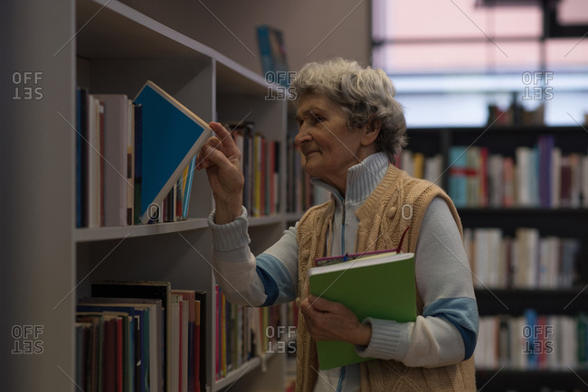 Senior woman removing book from book shelf in library