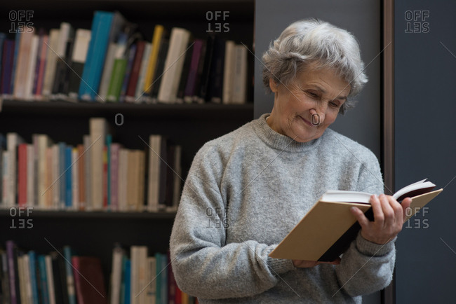 Active senior woman reading a book in library