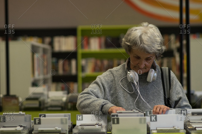 Senior woman choosing a dvd cassette in library