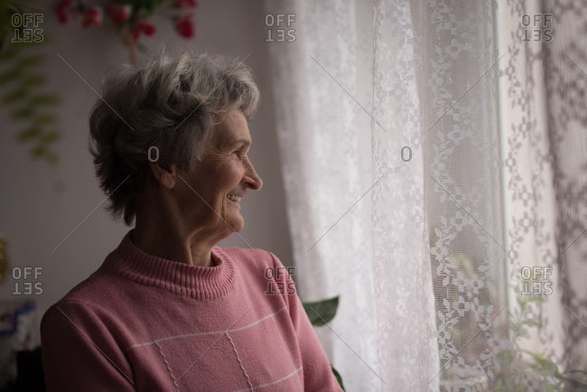 Thoughtful senior woman smiling at home