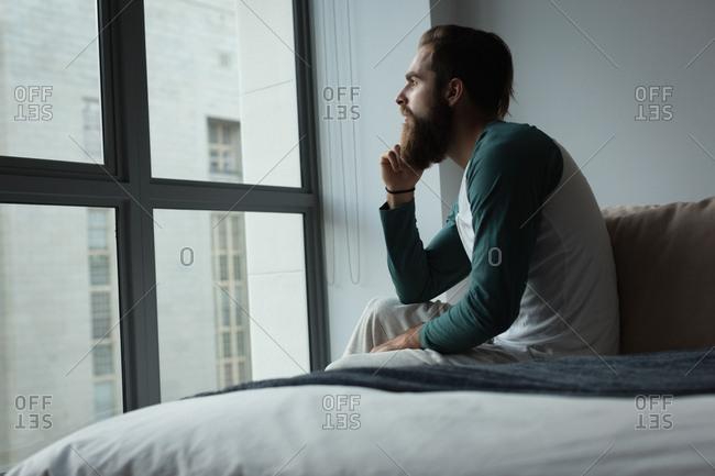 Man looking through window in bedroom at home