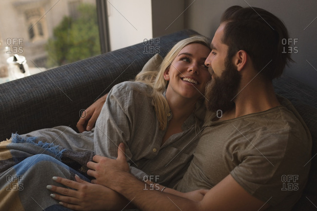 Couple embracing each other in living room at home