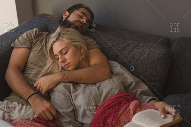 Couple sleeping in living room at home