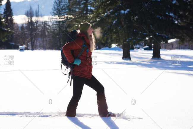 Woman walking on snow covered landscape on a sunny day