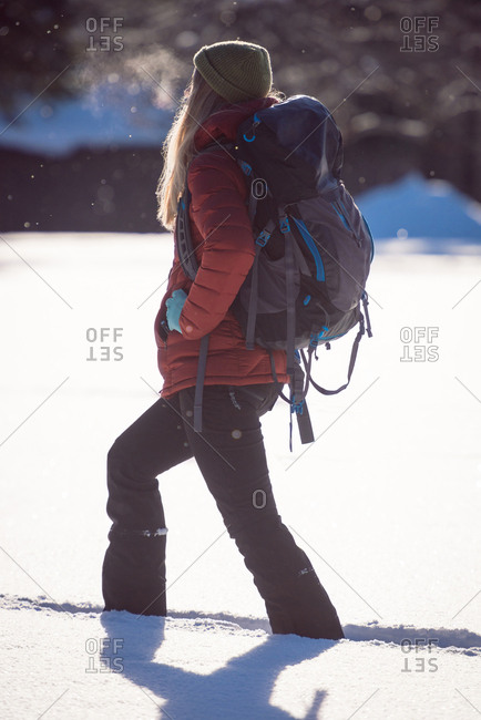 Woman walking on snowy landscape on a sunny day