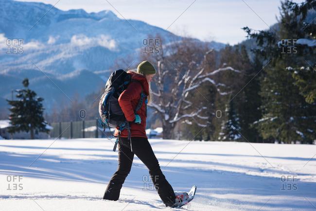 Woman walking on snowy landscape on a sunny day