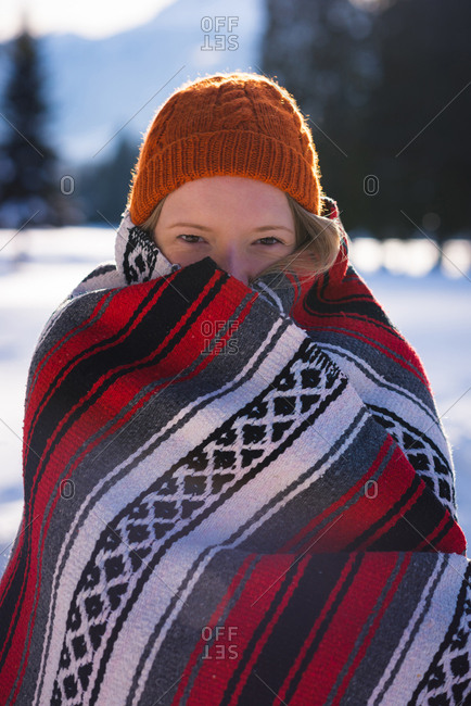 Smiling woman wrapped in blanket in snow