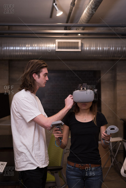 Male executive helping female executive in using virtual reality headset in office