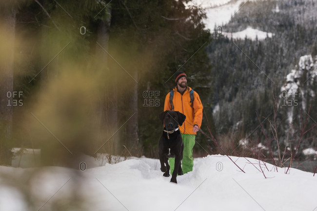 Man walking with his dog on a snowy landscape during winter