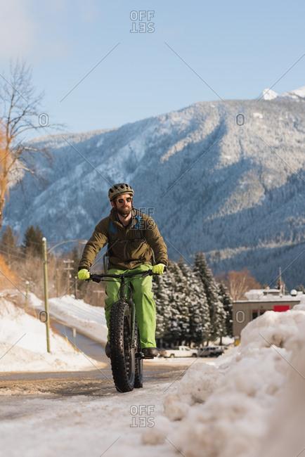 Man riding his bicycle on sidewalk during winter
