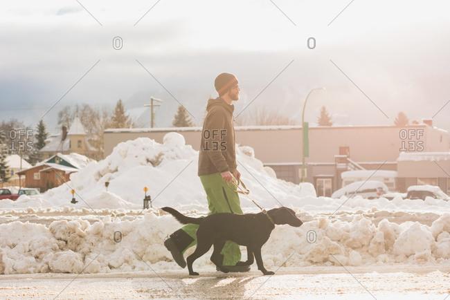 Man walking with his dog on sidewalk during winter