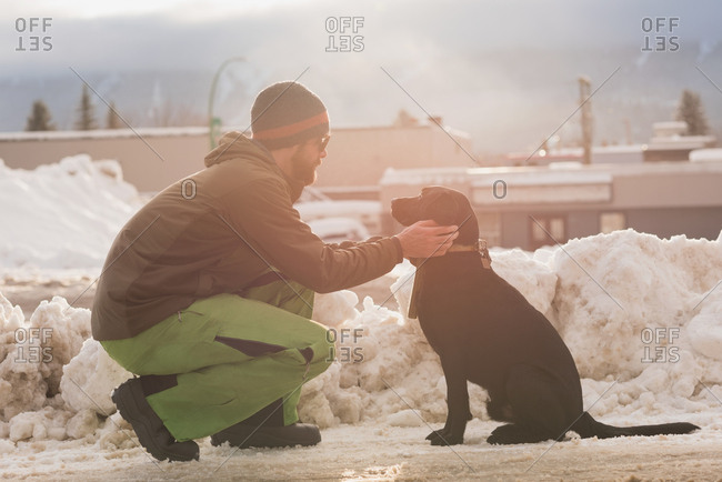 Man petting his dog on street side during winter