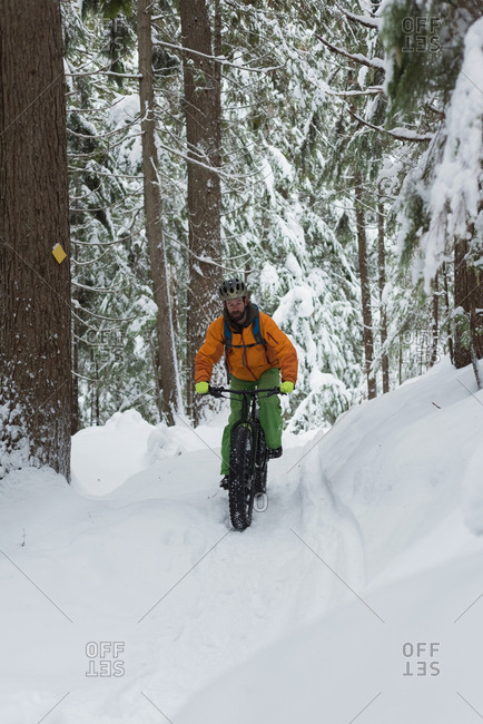 Man riding bicycle on a snowy landscape during winter