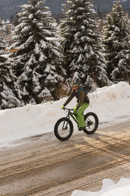 Man riding his bicycle on street during winter