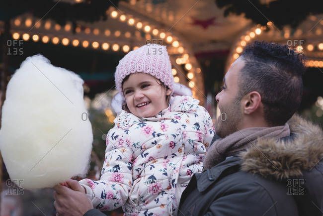 Father and daughter having cotton candy at dusk in amusement park