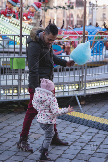 Father and daughter walking with cotton candy in amusement park