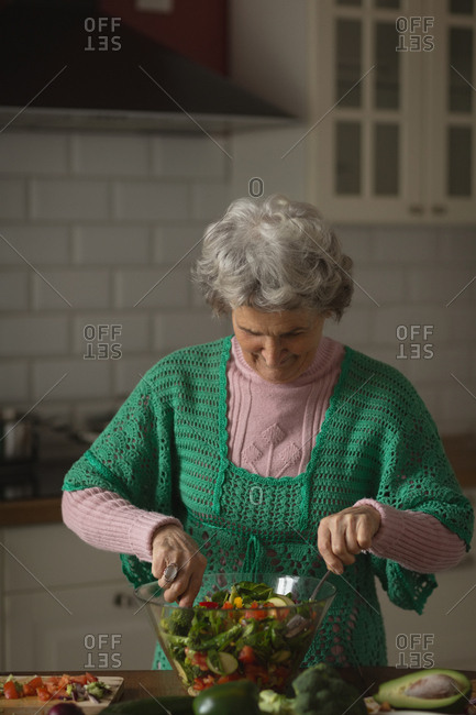 Senior woman preparing vegetable salad in kitchen at home