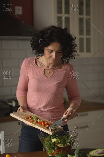 Woman preparing vegetable salad in kitchen at home