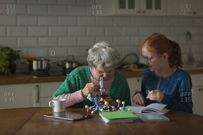 Grandmother with her granddaughter looking through microscope in kitchen at home