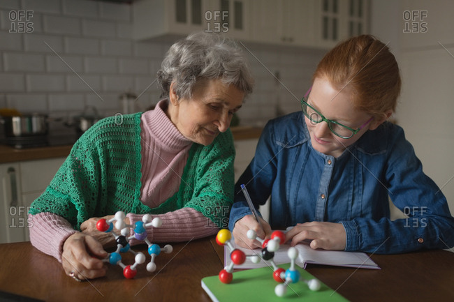 Grandmother helping granddaughter with homework in kitchen at home