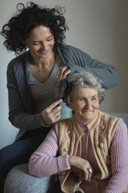 Daughter combing hair of her mother in living room at home