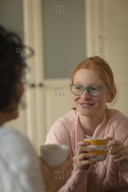 Mother and daughter having coffee in living room at home