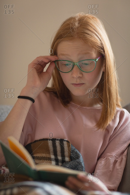 Girl reading a book in living room at home