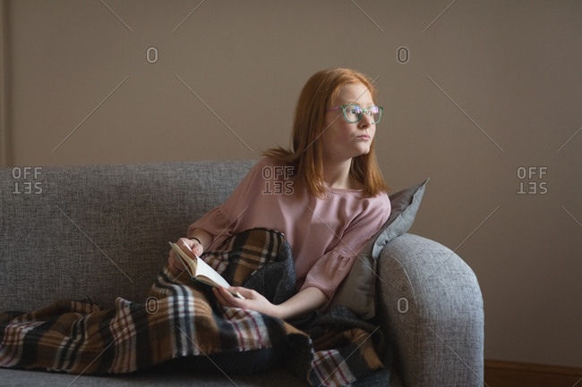 Thoughtful girl reading a book in living room at home
