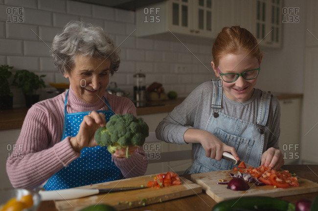 Grandmother and granddaughter cutting vegetables in kitchen at home
