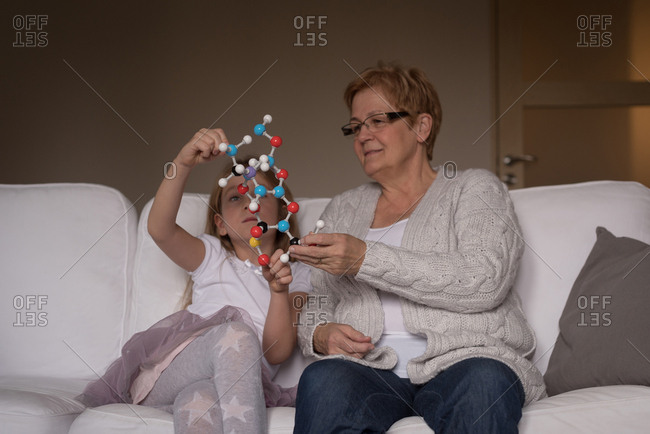 Grandmother and granddaughter playing with molecule model in living room at home