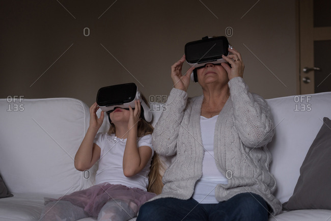 Grandmother and granddaughter using virtual reality headset at home