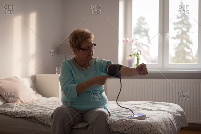 Senior woman checking blood pressure on a monitor at home