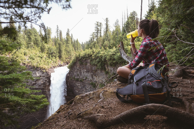Woman sitting near waterfall and drinking water on a sunny day