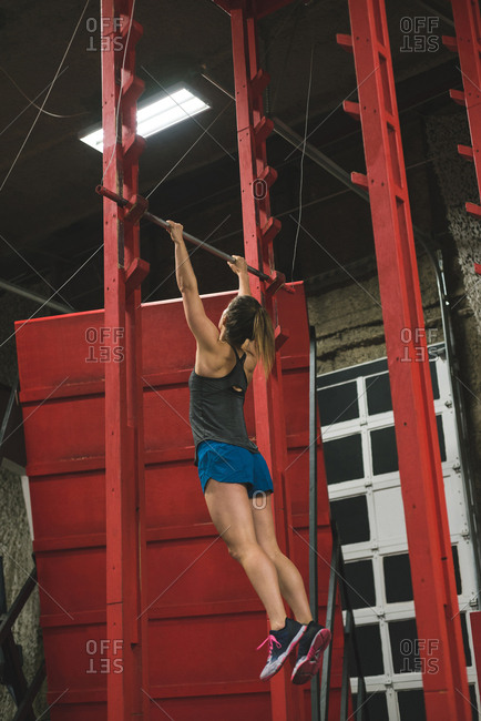 Rear view of muscular woman practicing pull up on a pull up bar