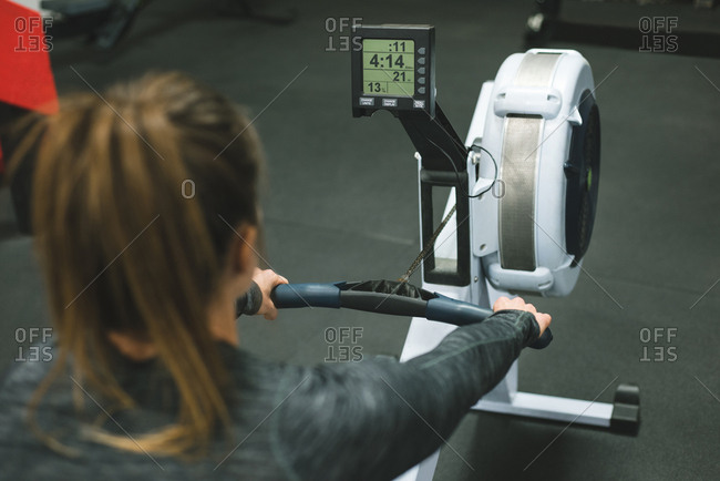 Rear view of muscular woman exercising on rowing machine at gym