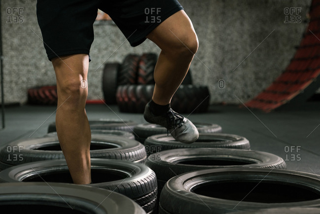 Low section of muscular man at tire jumping training in gym