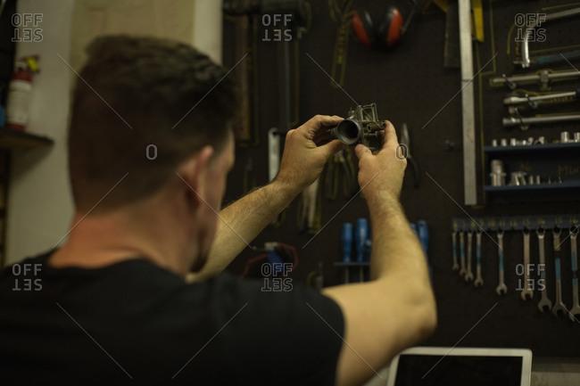 Mechanic checking motorbike parts in garage