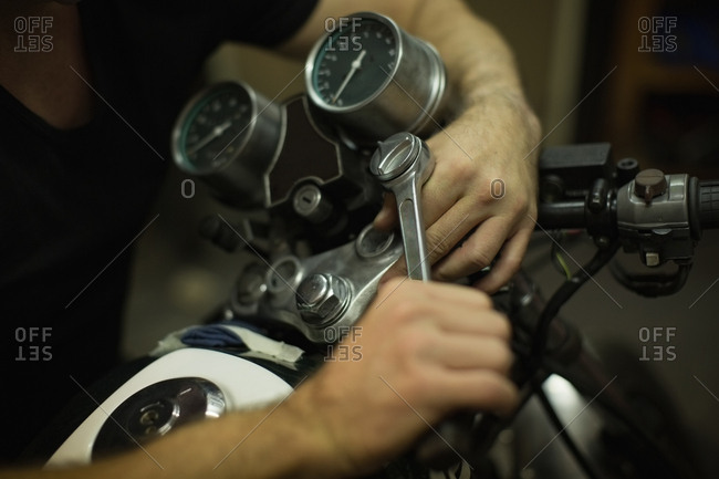 Mechanic tightening motorbike bike handle in garage