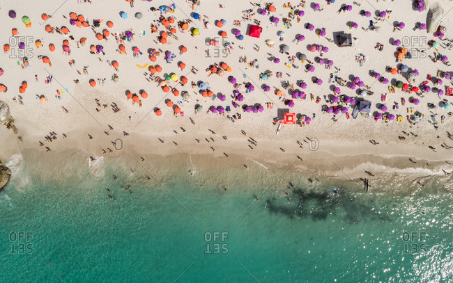 Aerial view of tourist sunbathing at beach on a sunny day