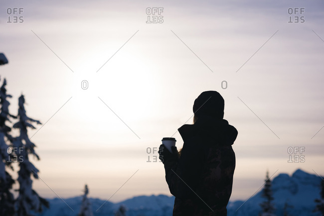 Woman with coffee looking at snow covered mountains at dusk