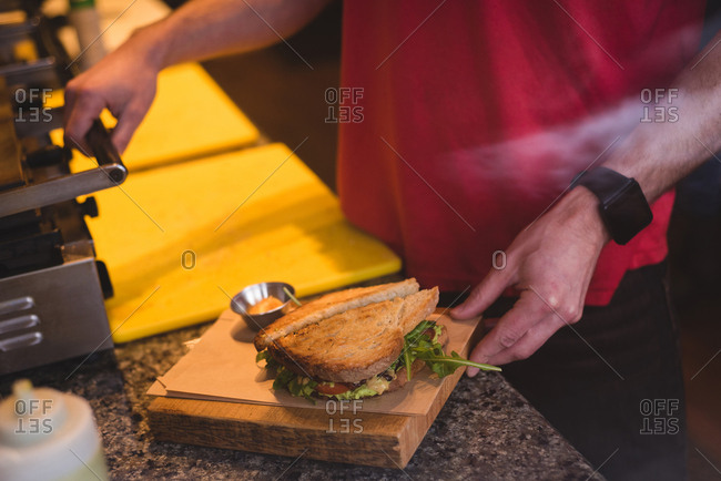 Close-up of male waiter preparing sandwich in cafe
