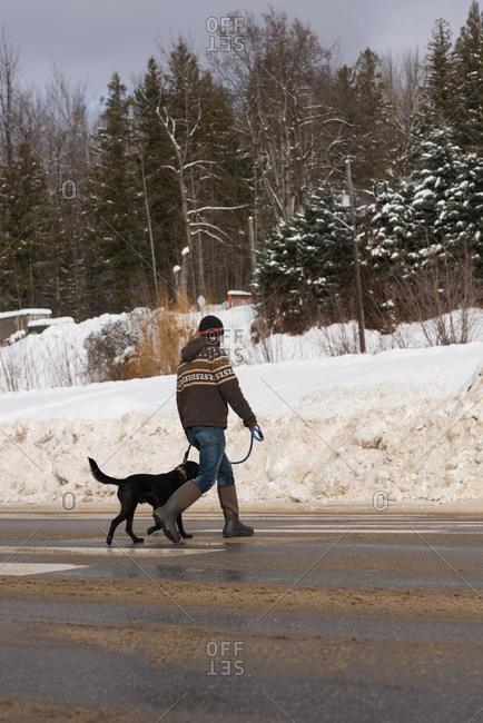 Man walking with his dog on street during winter