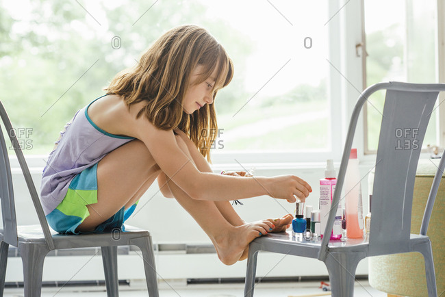 Full length of girl applying nail polish while sitting on chair at home