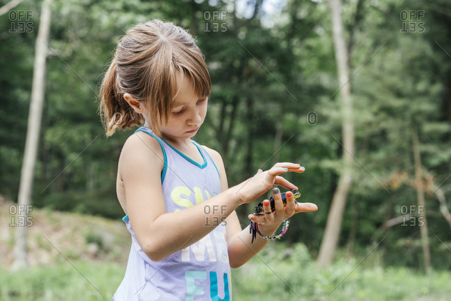 Cute girl holding frog while standing against trees at forest