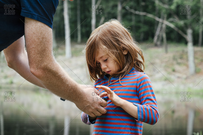 Father holding frog while son touching at lake in woods